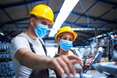 industrial-workers-with-face-masks-protected-against-corona-virus-discussing-about-metal-parts-in-factory